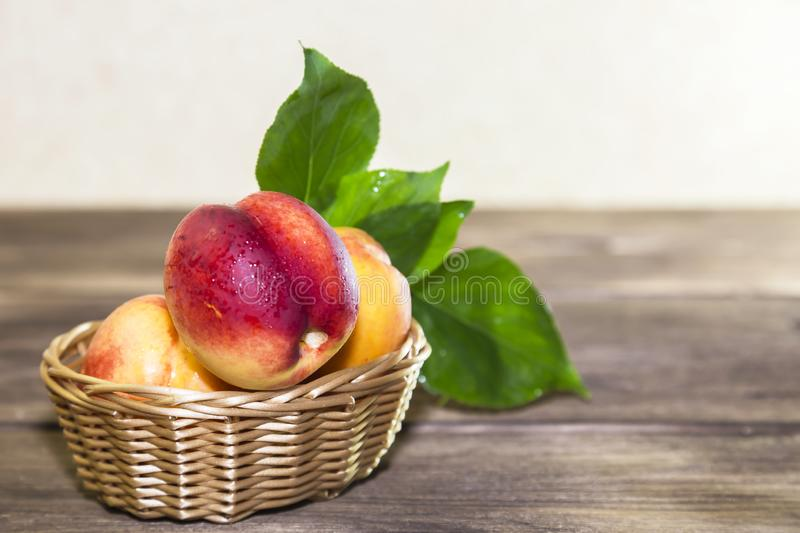 Food, harvest, fresh fruit. Ripe fruit of juicy peach with water drops and leaves in a wicker basket on a wooden background in a royalty free stock photo