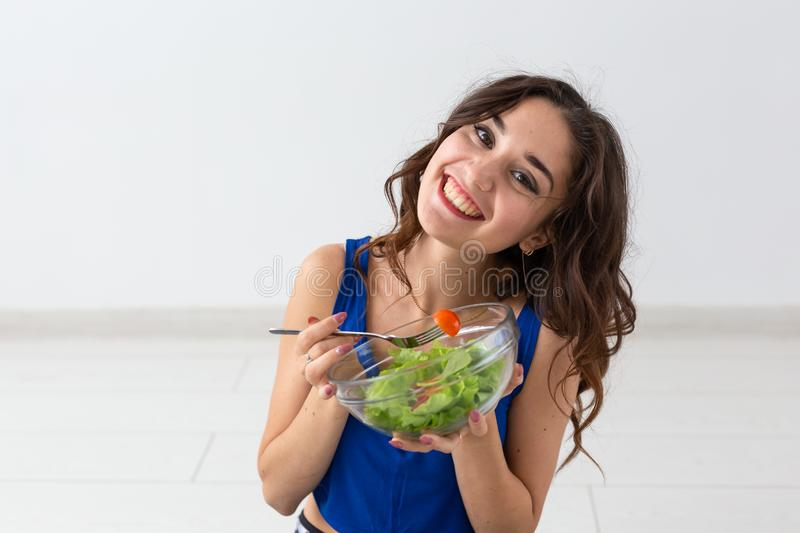 Food, healthy lifestyle, people concept - Young woman eating salad and smiling stock image