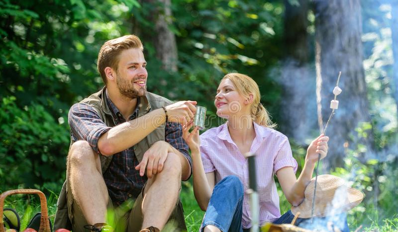 Food for hike and camping. Couple sit near bonfire eat snacks and drink. Weekend picnic. Couple take break to eat nature. Background. Couple in love camping royalty free stock images