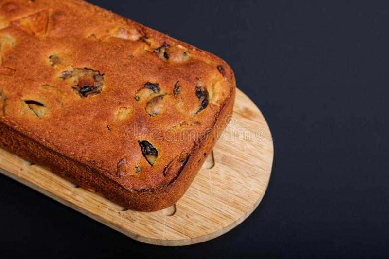Food Homemade fruits cake loaf on wooden board. With black background royalty free stock images