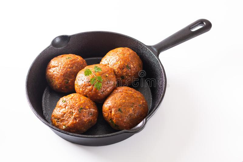 Food Homemade raw organic spicy meatball in iron cast on white background royalty free stock images