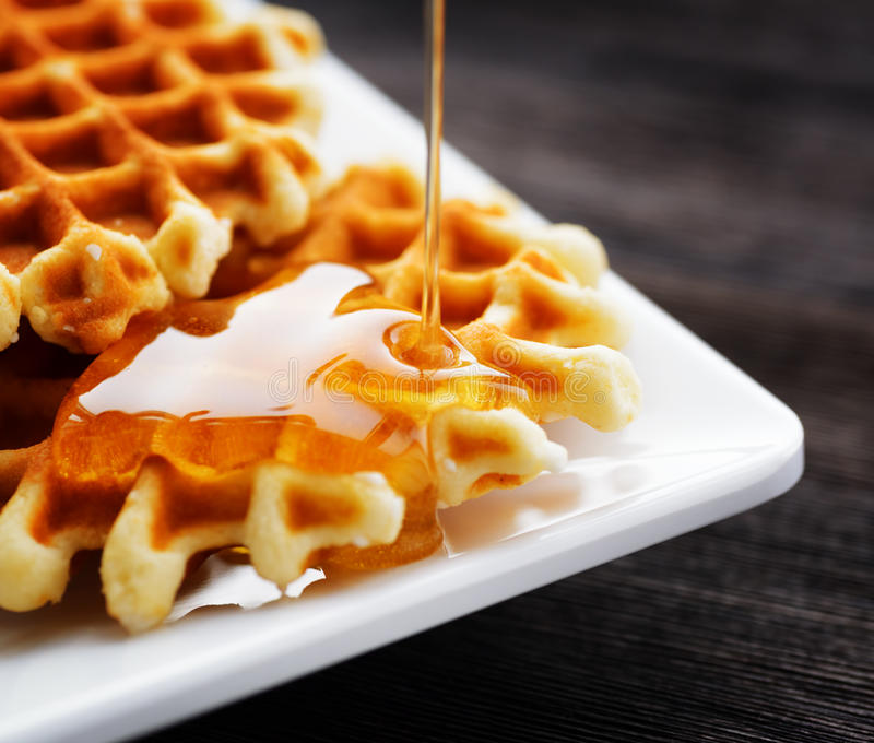 Honey pouring on a fresh waffles.  royalty free stock images