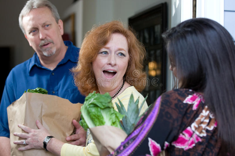 Food For Hungry. A look of surprise emotion is on the recipients faces as a charity relief worker brings bags of food and groceries to the hungry royalty free stock image