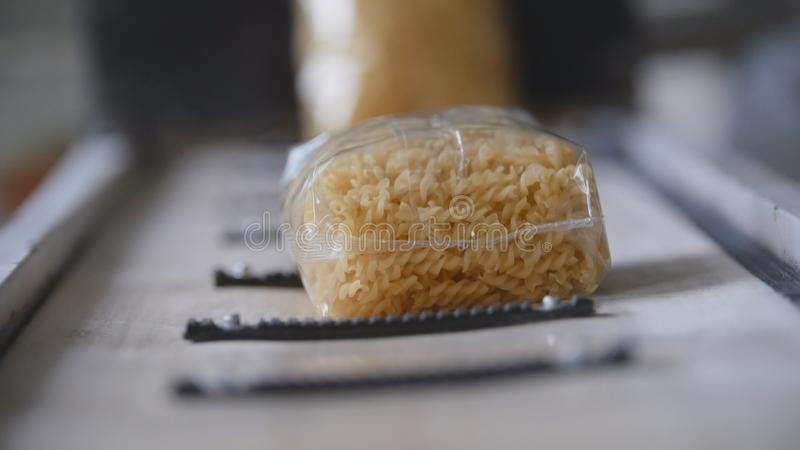 Food industry - conveyor with plastic pack of macaroni stock photos