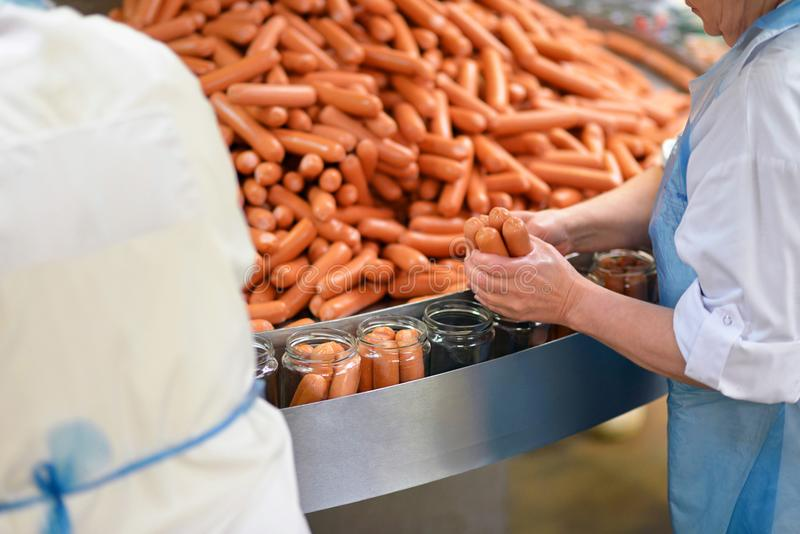 Food industry: workers in the production of original German brat. Wurst in a large butcher`s shop royalty free stock images