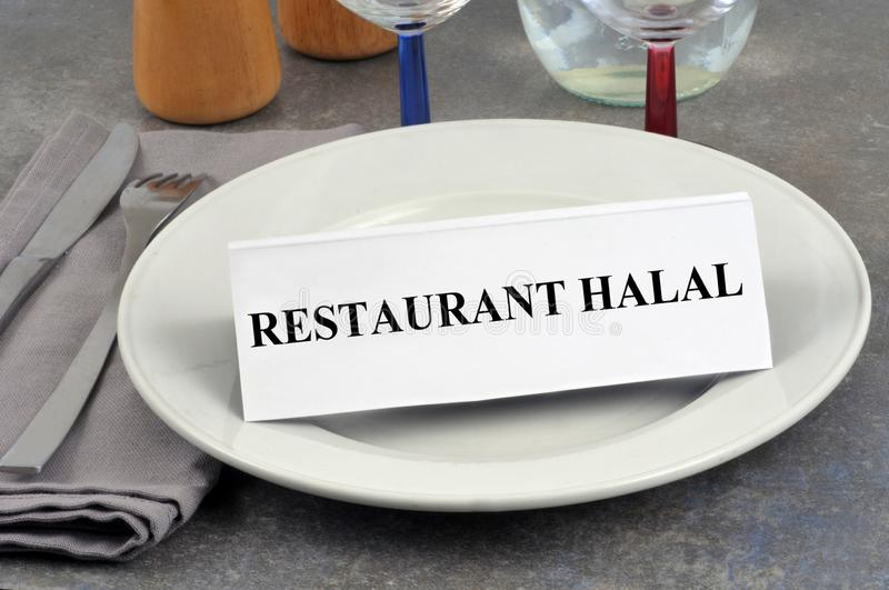 Halal restaurant written in French on a cardboard placed on a plate royalty free stock photography