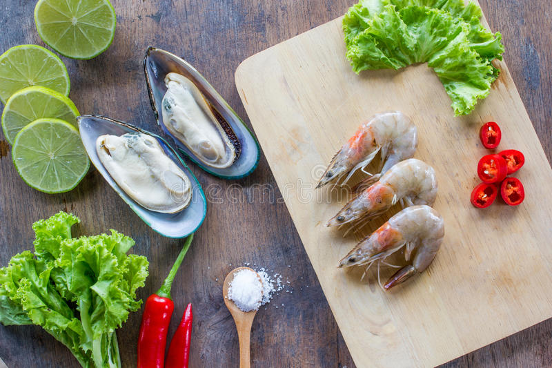 Food ingredient background. New Zealand mussel, shrimp, peppers, salad, salt , wood plate lime or lemon on table stock photos