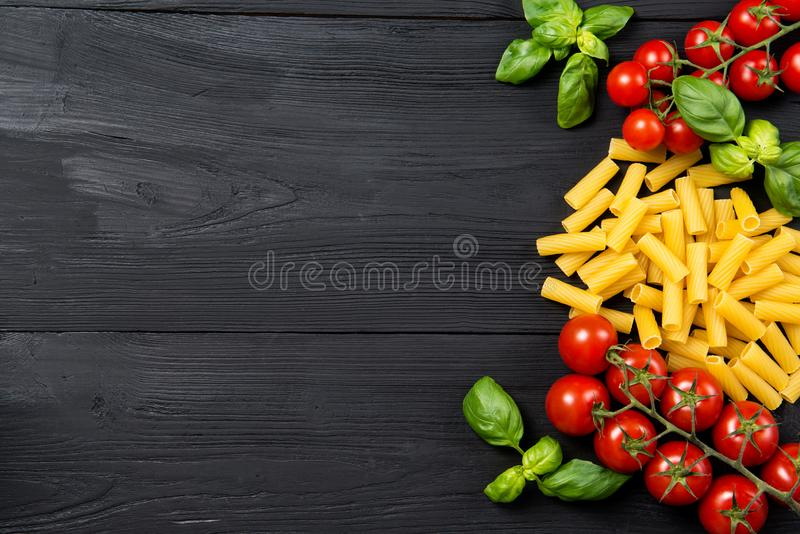 Food ingredients for Italian tortiglioni pasta with cherry tomatoes and basil leaves, black wooden background, top view with copy stock photo