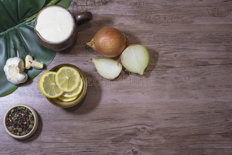 Food ingredients lemon slices onion yogurt garlic spices on a wooden table with a space in the right for written royalty free stock photo