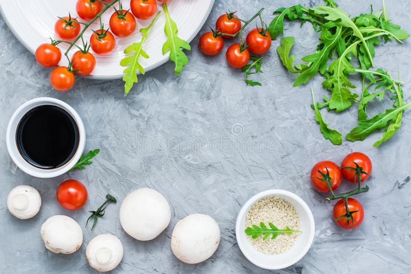 Food ingredients lined frame on a concrete background: cherry tomatoes, mushrooms, arugula, sesame and balsamic sauce royalty free stock photos