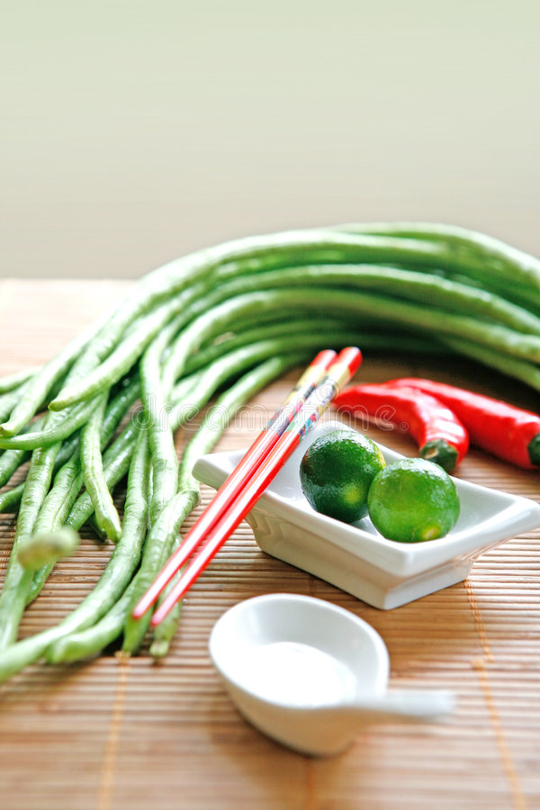 Food ingredients of long beans and limes. Oriental food ingredients of long beans, calamansi limes and red chilis on bamboo mat with red chopsticks and ceramic royalty free stock photos