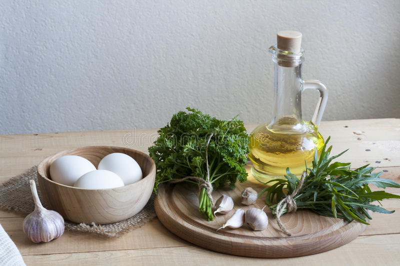 Food ingredients. Oil, eggs, garlic and herbs on wooden table. Wooden board and napkin royalty free stock photography