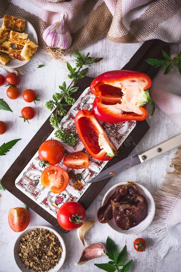 Food Ingredients for preparing Meal with Red Pepper, Tomatoes, Coppa Ham, Halloumi and Dukkah Spices royalty free stock photography