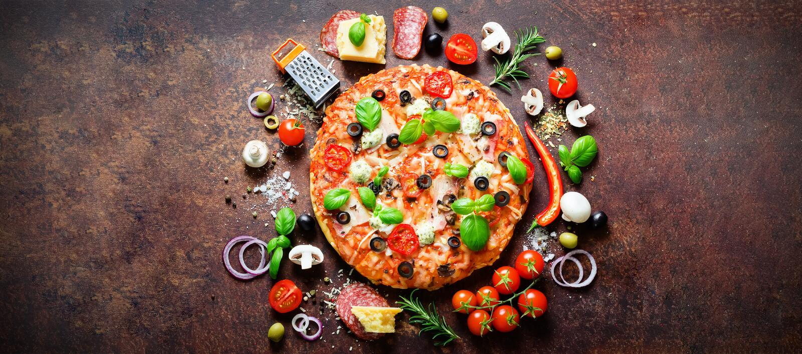 Food ingredients and spices for cooking delicious italian pizza. Mushrooms, tomatoes, cheese, onion, oil, pepper, salt. Basil, grater, olive on rustic stock images