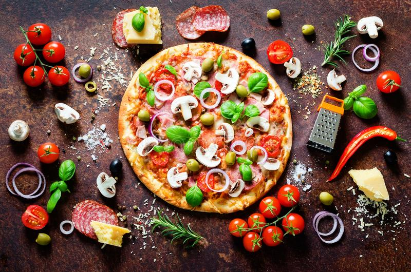 Food ingredients and spices for cooking delicious italian pizza. Mushrooms, tomatoes, cheese, onion, oil, pepper, salt. Basil, grater, olive on rustic