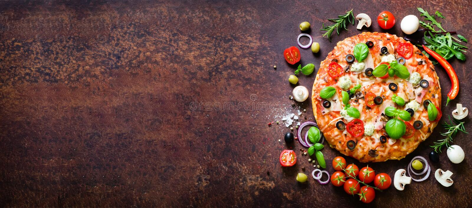 Food ingredients and spices for cooking delicious italian pizza. Mushrooms, tomatoes, cheese, onion, oil, pepper, salt. Basil, olive on rustic background stock image