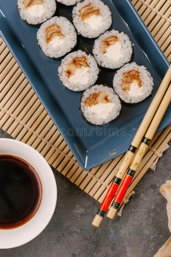 Food in a japanese restaurant. Selective focus Close up rolls with tuna on a black rectangular plate on the grey stock photography