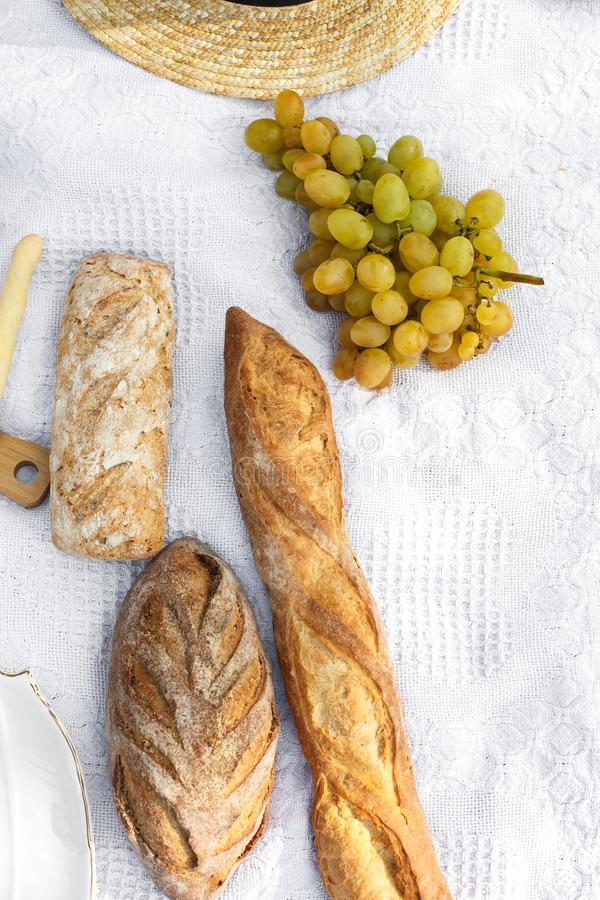 Food lay out on picnic blanket. fresh baked bread, grapes, olives and photocam lay on white blanket. Picnic prepare decoration.  stock images