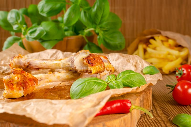Food leftovers from grilled chicken and chilli with tomato, fries and basil on wooden background stock photography