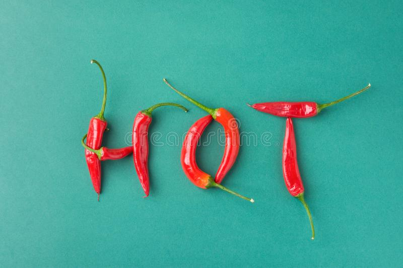 Food Lettering Typography. Word Hot Made from Red Spicy Chili Peppers on Green Background. Mexican Italian Spanish Greek Cuisine. Food Lettering Typography. Word stock image