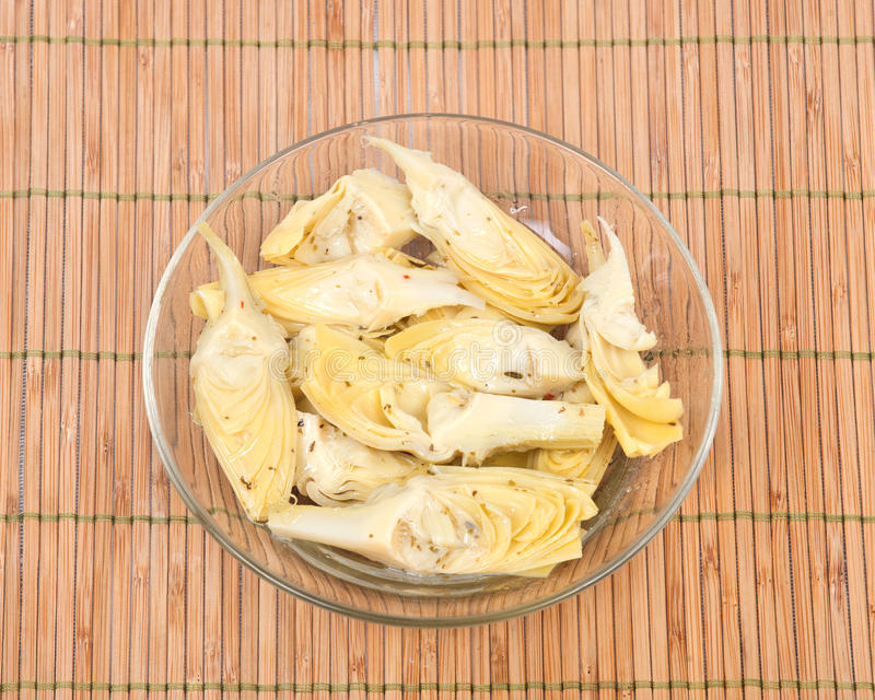 Food of love, marinated artichokes. In bowl on bamboo placemat stock photo