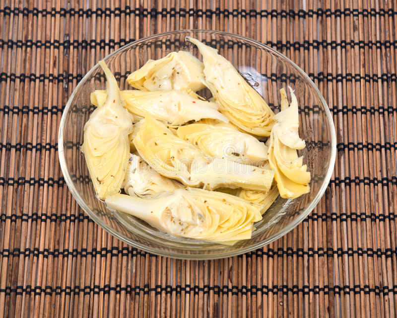 Food of love, marinated artichokes. In bowl on bamboo placemat royalty free stock photography