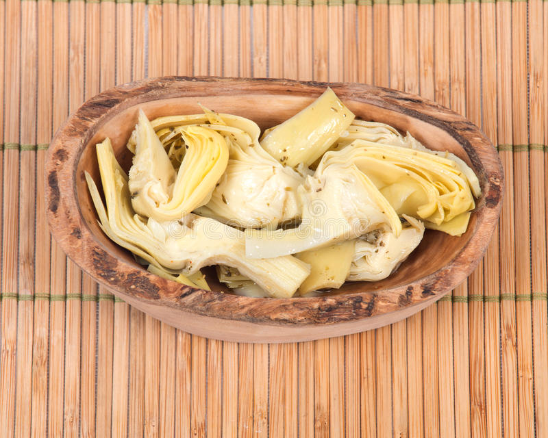 Food of love, marinated artichokes. In olive wood bowl on bamboo placemat royalty free stock photos