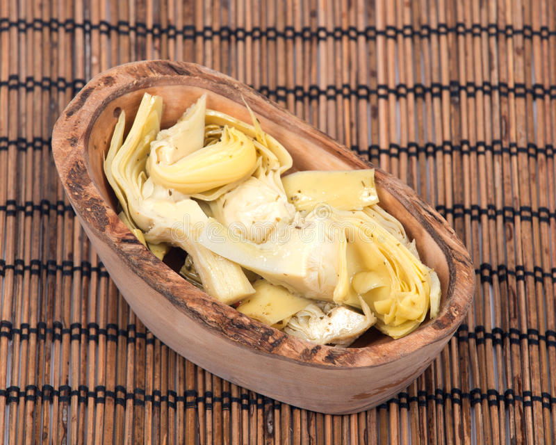 Food of love, marinated artichokes. In olive wood bowl on bamboo placemat royalty free stock photo