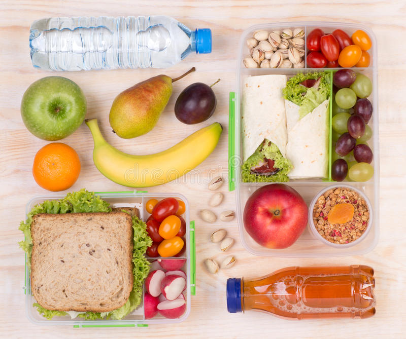 Food for lunch, top view. Food for lunch, lunchboxes with sandwiches, fruits, vegetables, and drinks, top view stock images
