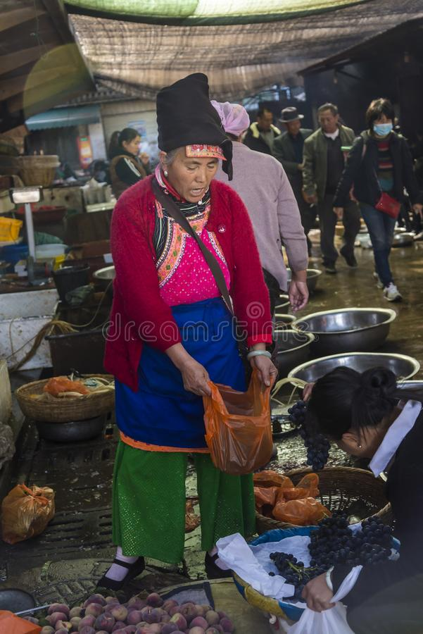 Bai woman market seller dressed in ethnic costume, Dali Old Town,  China. Food market, Bai woman market seller dressed in ethnic costume, Dali Old Town, Yunnan royalty free stock images