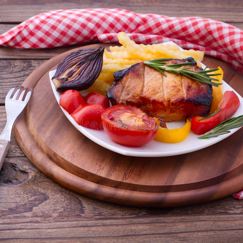 Food. Meat barbecue with vegetables. On wooden surface. Meat steak. Beef steak bbq. Tomatoes, peppers, spices for cooking meat royalty free stock images