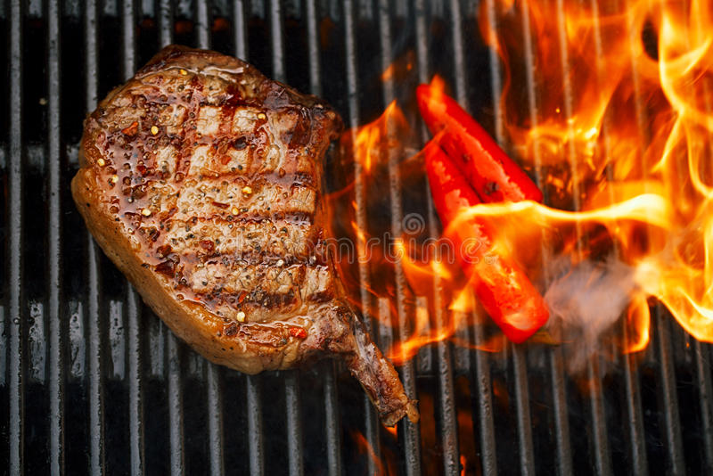 Food meat - beef steak on bbq barbecue grill with flame. Shallow dof royalty free stock photography