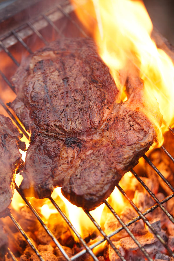 Food meat - rib eye beef steak on party summer barbecue grill wi. Th flame. Shallow dof stock photography