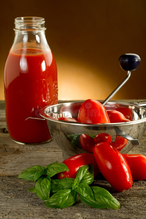 Food mill with tomatoes. And sauce stock image