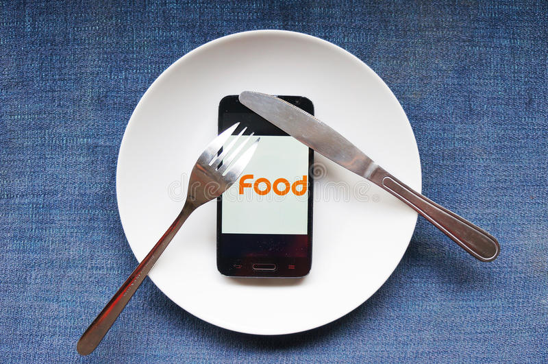 Food for modern people. Nowadays, more and more people regard cell phone as the most important thing in their life. It's the only thing they care about and royalty free stock image