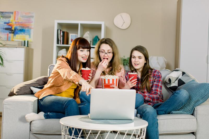 Food and movies. Three emotional pretty sisters eating popcorn when watching movie or sport program while sits on the stock image