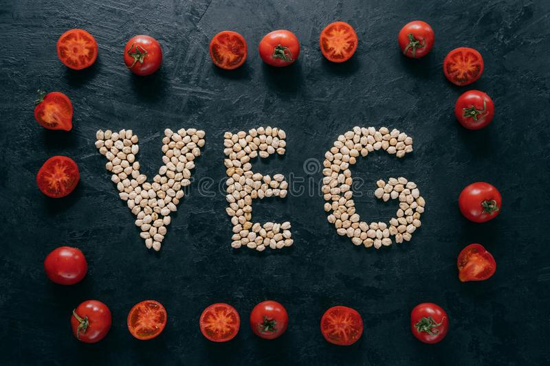 Food and nutrition concept. Horizontal shot of dry garbanzo in form of letter VEG, denoting products for vegans. Tomato frame stock photo