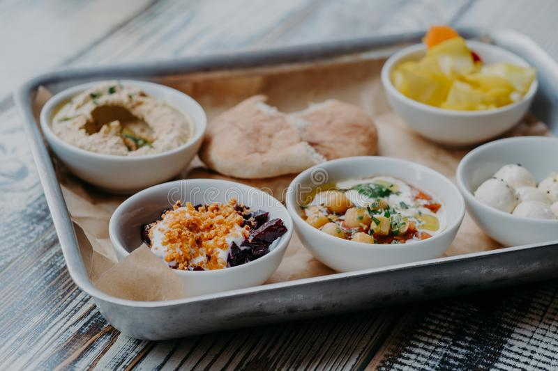 Food and nutrition concept. Traditional Israel dish for dinner. Tray of delicious hummus, beet with spices, core of tomatoes, pita. Bread, goat cheese served royalty free stock image