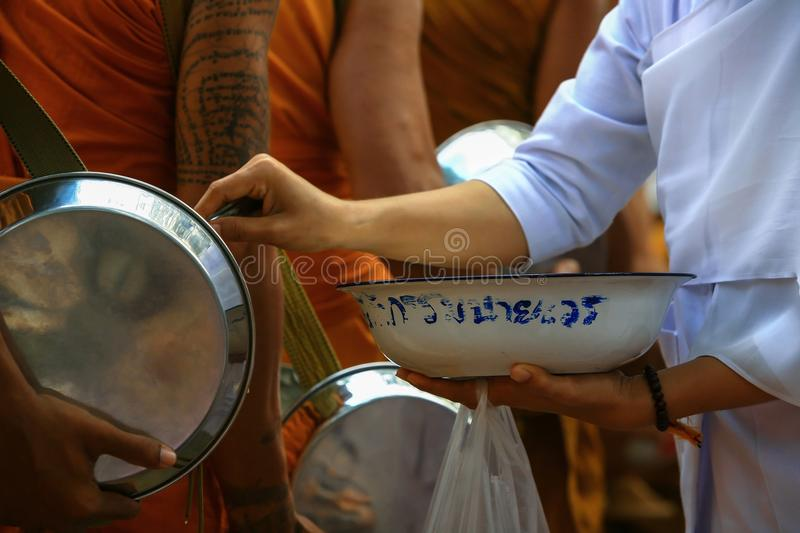 Food offering by buddhist Thai female to the monk royalty free stock photos