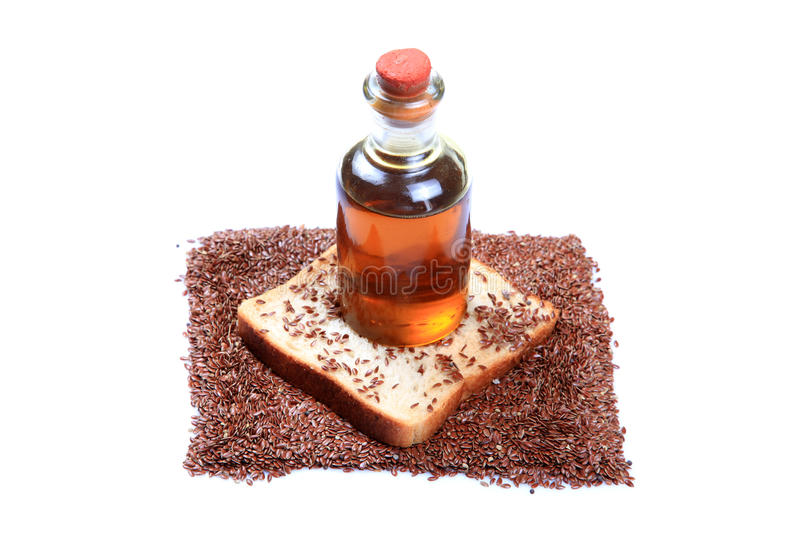 Food and oil. Fibrous food brown bread slice with roasted flax seeds and oil bottle isolated on white background royalty free stock photo