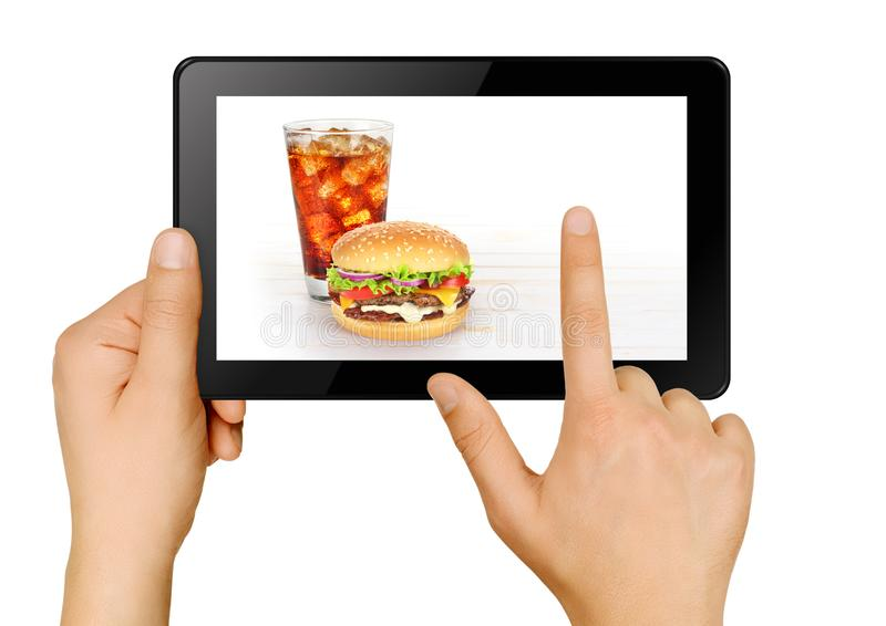 Food ordering with tablet. Hands with tablet ordering burger and cola online. Food delivery concept. Isolated on white royalty free stock photography