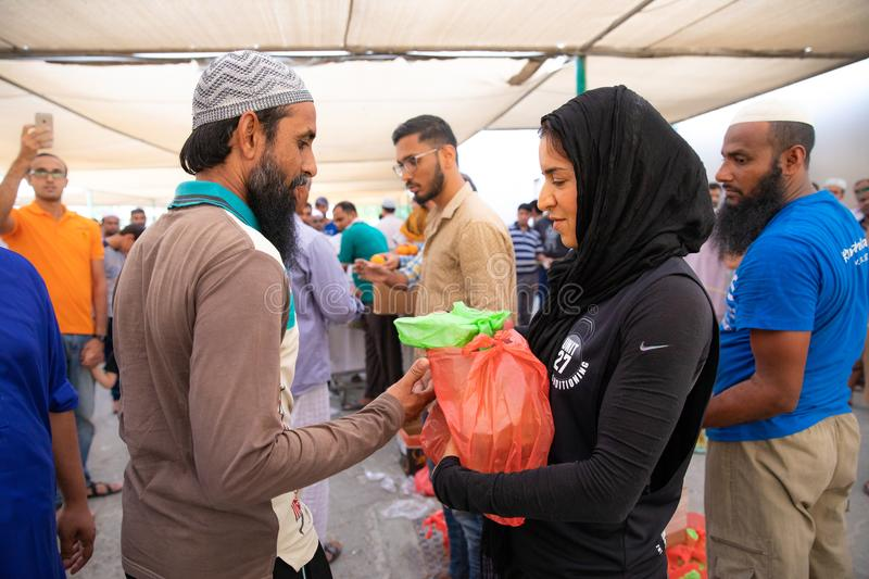 Food packages` distribution in mosque during Ramadan iftar meal. Dubai, UAE - May 18, 2018: Volunteers distributing food packages to workers during iftar meal stock photo