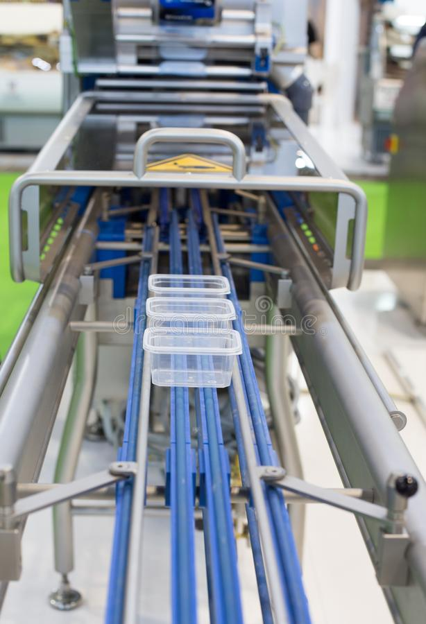 Food packaging machine. Plastic boxes on conveyor belt of food packaging machine royalty free stock images