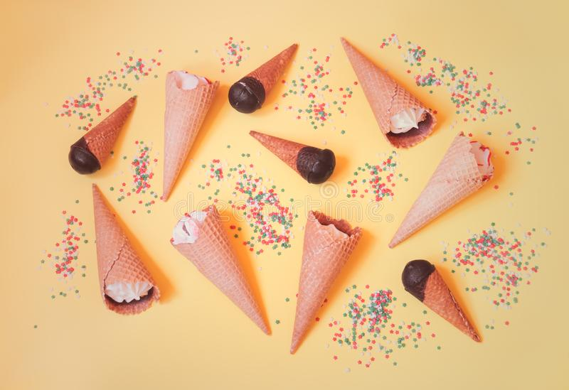 Food pattern made of vanilla ice cream cones and sugar sprinkle stars on yellow background royalty free stock images