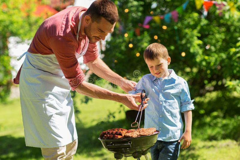Father and son cooking meat on barbecue grill stock image