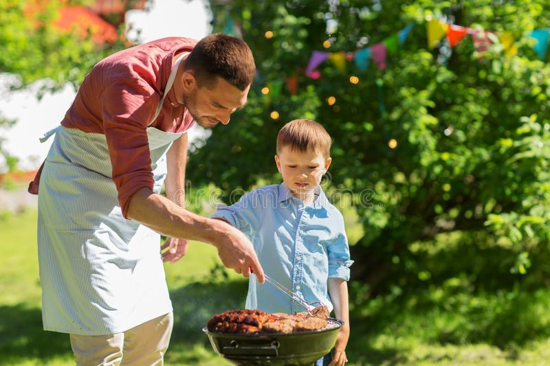 Father and son cooking meat on barbecue grill. Food, people and family time concept - father and son cooking meat on barbecue grill at bbq party in summer garden royalty free stock photography