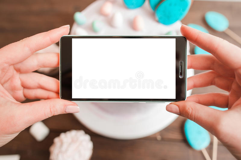 Food photo of cake by smartphone. Blank screen. Food photography of white cake on wooden table background. Smartphone mockup with blank screen. Small business stock photos