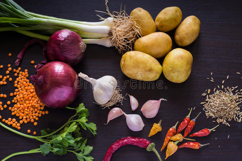 Food photo with fresh organic vegetables and spices on dark wooden rustic background, top view. royalty free stock images