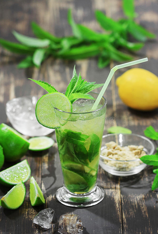 Food Photo minty mojito. Food Photo soft minty mojito on a dark wooden background in a tall glass with a straw, mint leaves, ice, pieces of lime, lemon in the stock photo