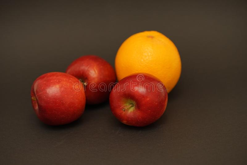 Red apple and orange on black background. Food photography. apple and orange capture in flash light stock image